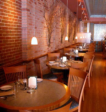Interior photo of tables and a red brick wall.